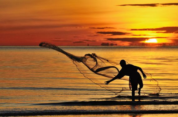 Fishierman throwing net in Hua Hin beach, in the morning, Thailand.